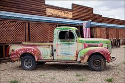 Photograph of old rusty truck and American flag in front of